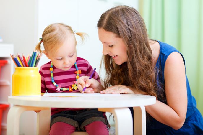 Une assistante maternelle jouant avec une petite fille.