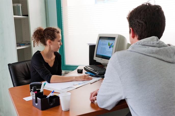 Une assistante sociale en entretien avec un jeune sans emploi.