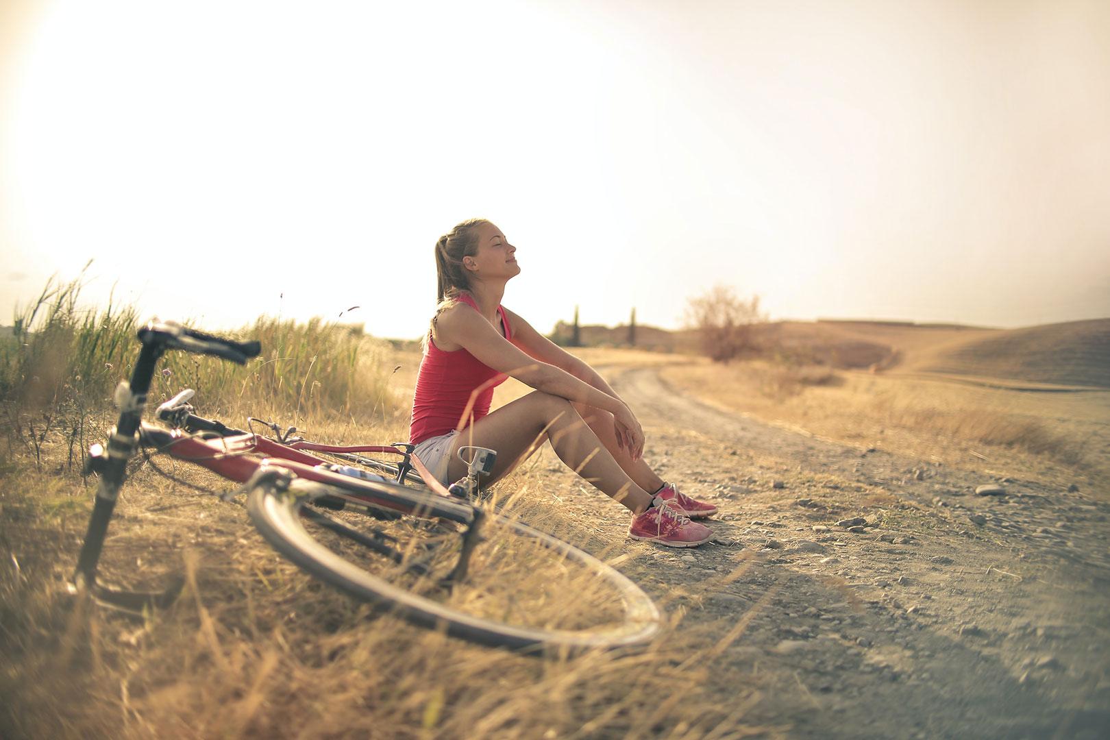 Une femme est à côté de son vélo, elle fait une balade en nature