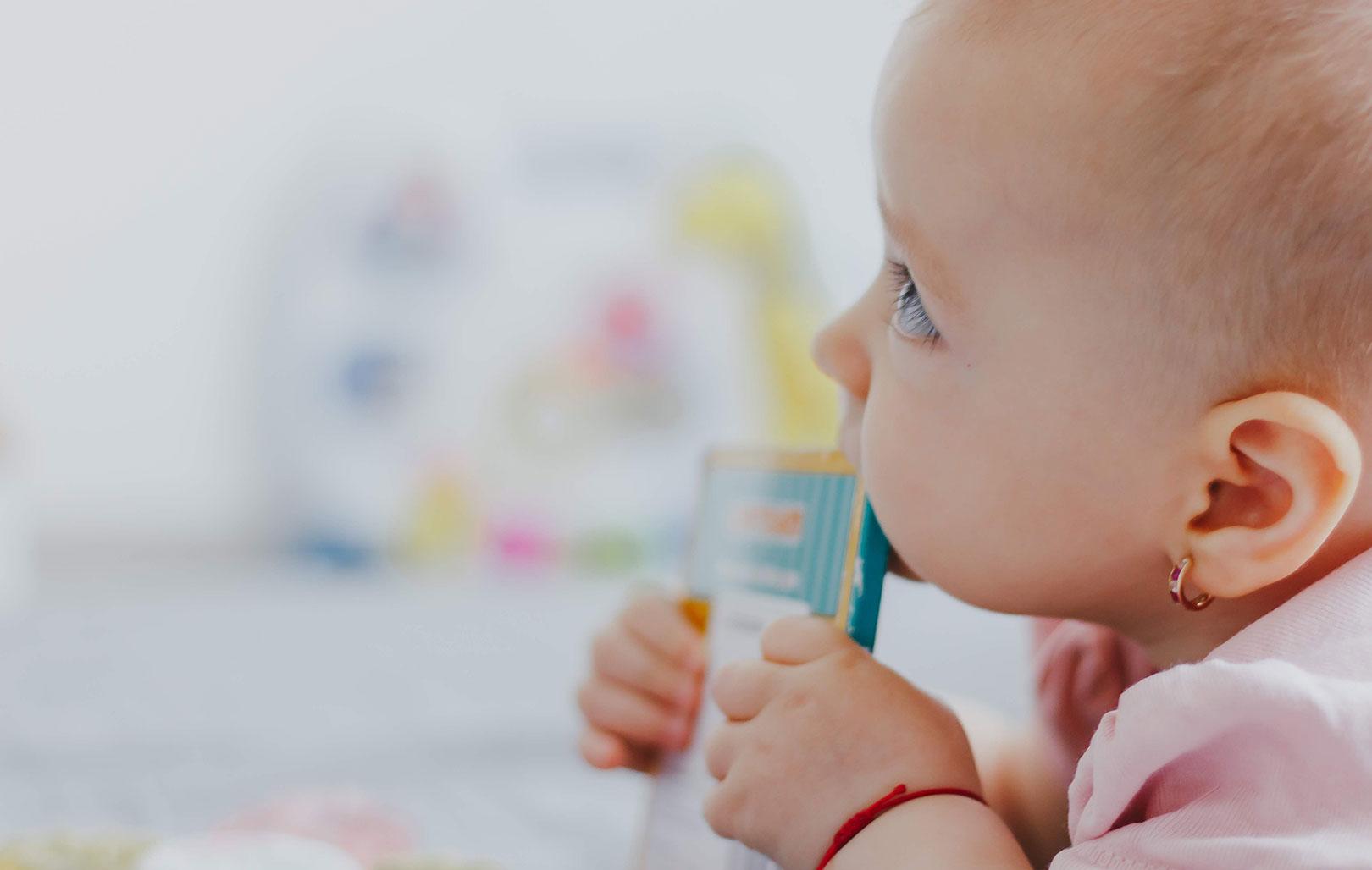 Un bébé croque un papier de médicament