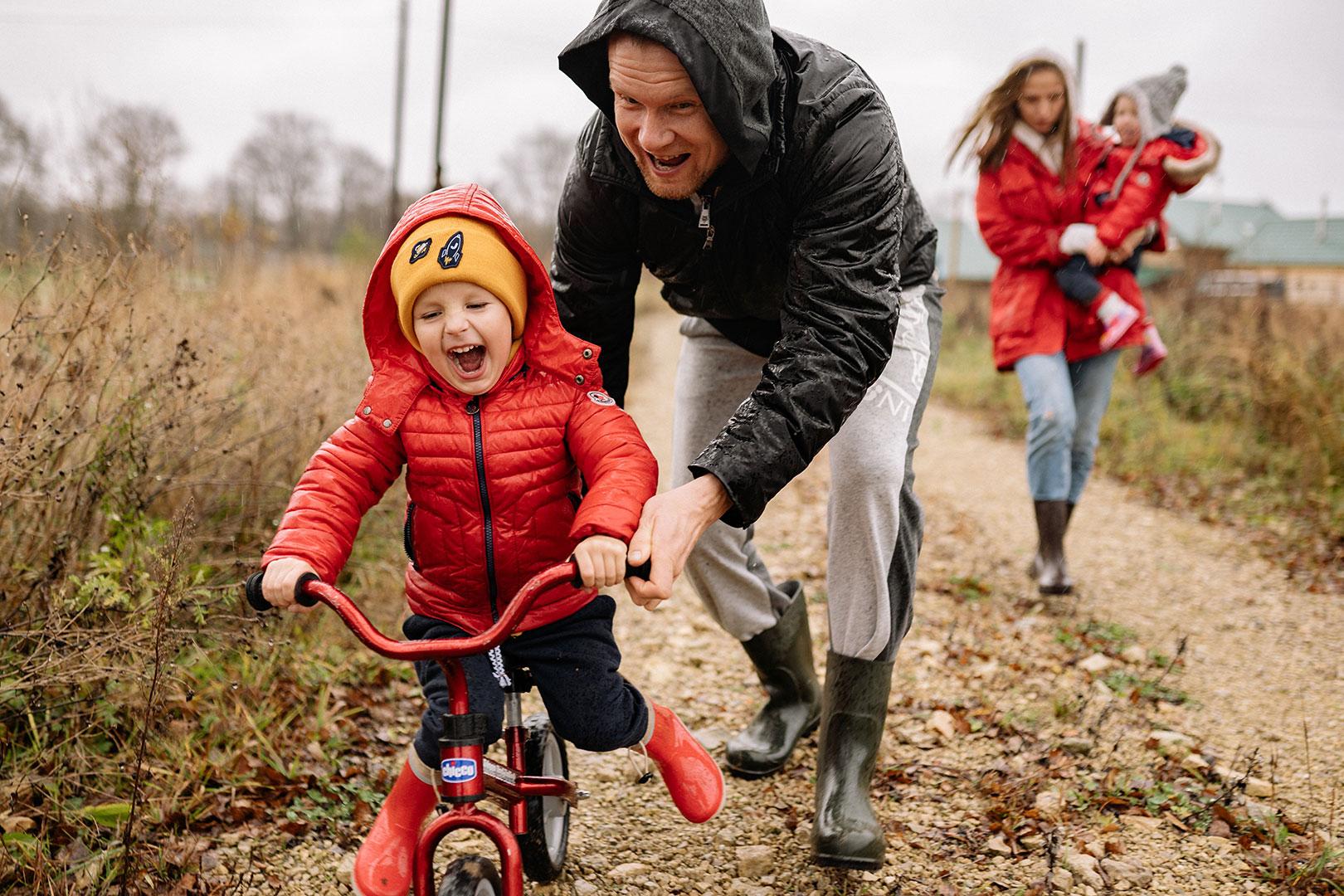 Un enfant avec un manteau rouge, un bonnet jaune est sur son vélo, son papa le pousse et sa maman est en arrière plan, elle porte un enfant.