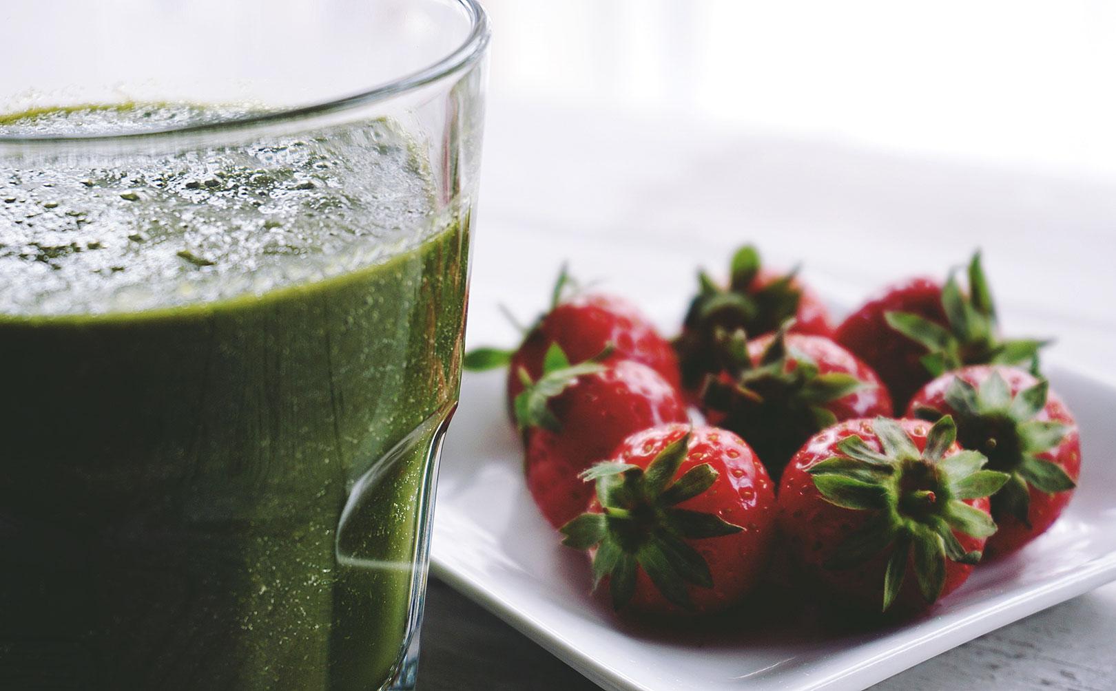 Un verre de smoothie au kiwi accompagné d'une assiettes de fraises fraiches